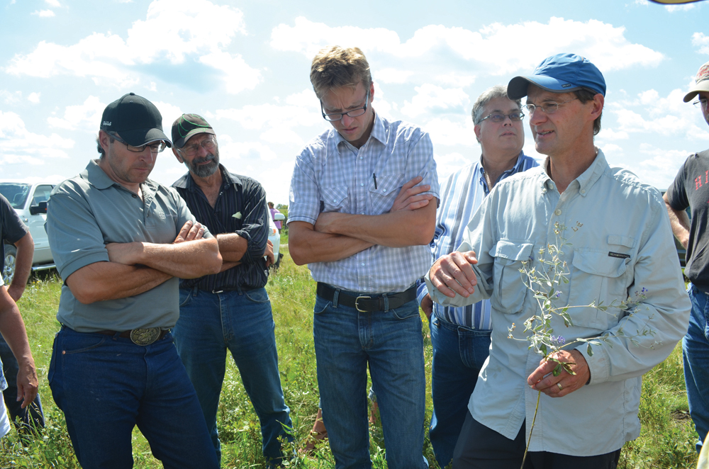 Manitoba grazing club co-ordinator Michael Thiele (r) discusses the importance of ground cover when looking to develop biological activity in soil.