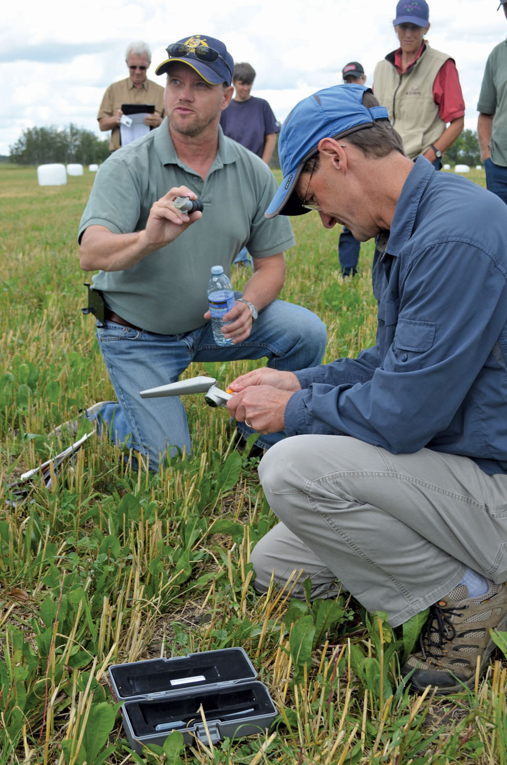 Clayton Robins (l) and Michael Thiele (r) test the sugar levels of Robins' pasture plants during his farm tour.