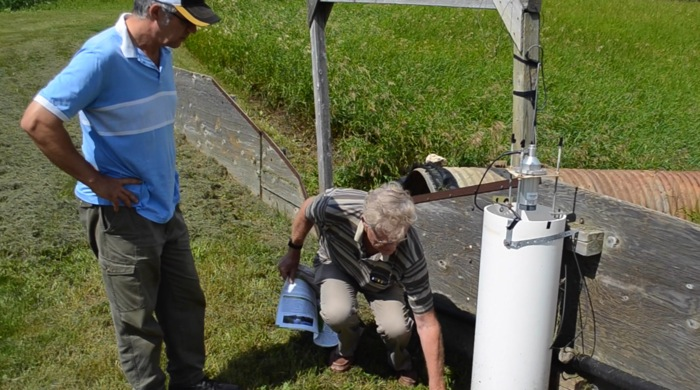 Don Cruikshank demonstrates how field runoff water samples are collected.