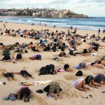 """A group of around 400 demonstrators participate in a protest by burying their heads in the sand at Sydney's Bondi Beach Nov. 13. Hundreds of protesters participated in the event, held ahead of the Nov. 15 G20 summit in Brisbane, which was being promoted as a message to Australian Prime Minister Tony Abbott's government that, """"You have your head in the sand on climate change."""""""