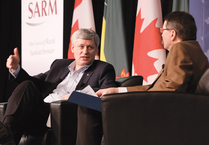 Stephen Harper in a discussion at a conference