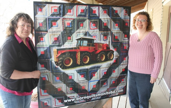 two women standing with decorative tractor quilt