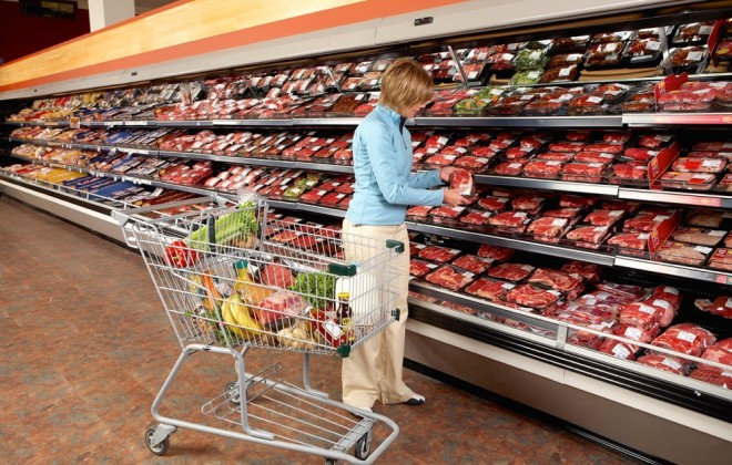 shopper at a beef display in grocery store