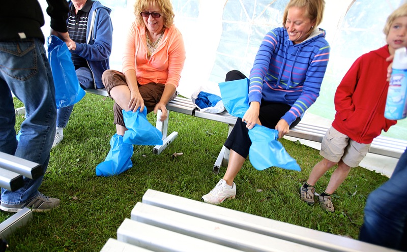 Visitors to Newest Poultry Farms Inc. don protective footwear on Open Farm Day.