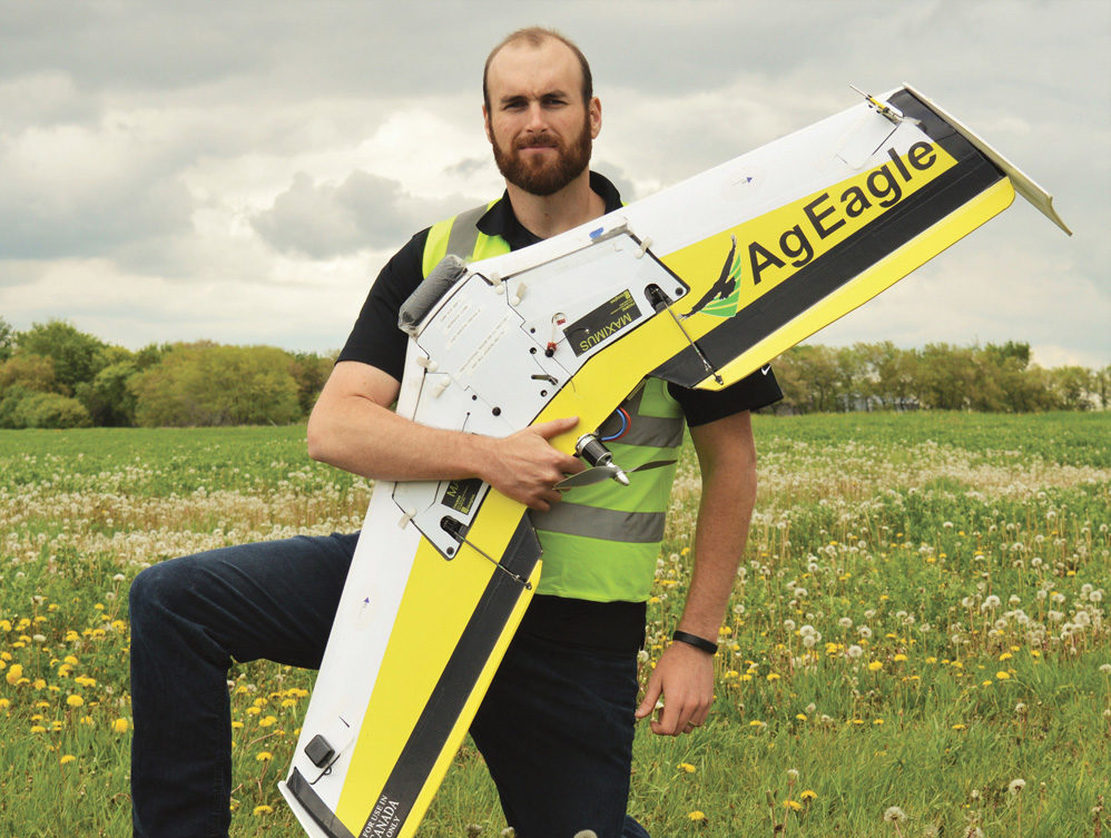 Matthew Johnson, founder of M3 Aerial Productions, poses with his fixed-wing drone, one of several his company uses to provide drone services to farmers since the agricultural branch of his company launched last year.