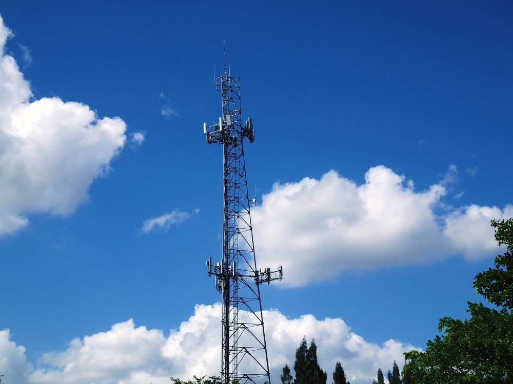 Communications Tower with blue sky and clouds in the background.