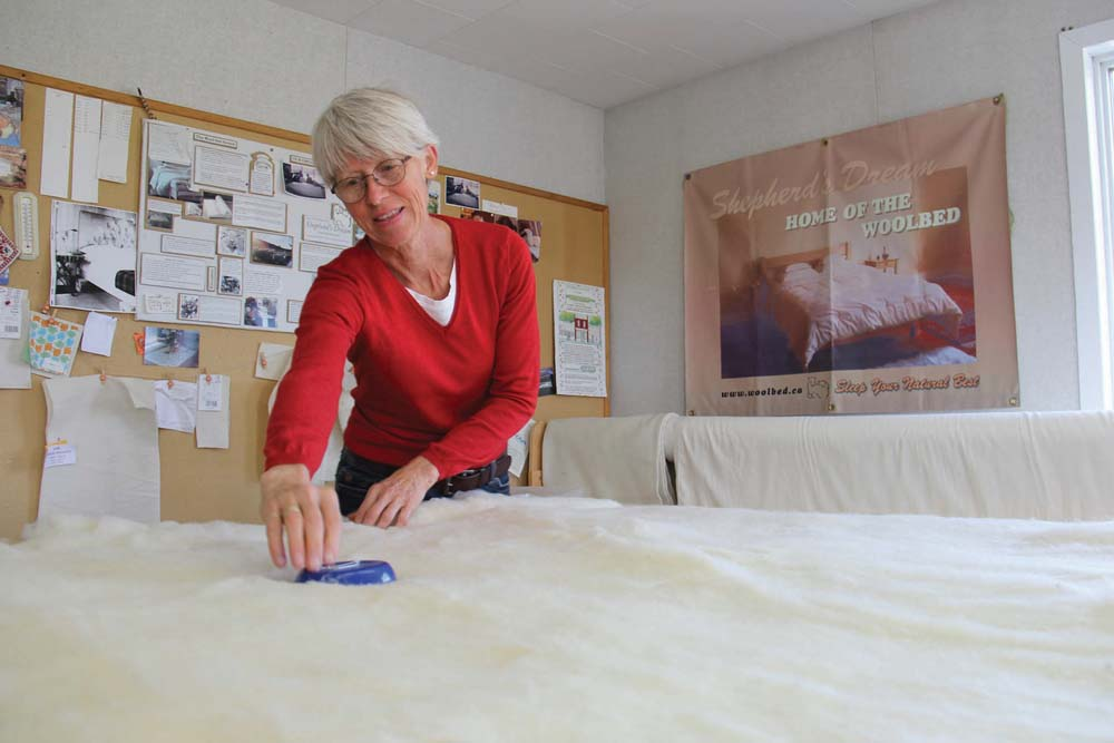Janet Kroeker applies a wool batt to cotton encasement fabric as she works on product line for the family's Rosa-area home-based business, Shepherd's Dream.