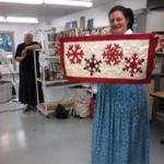 Andrea Maendel shows a snowflake table runner while Anna Maendel 