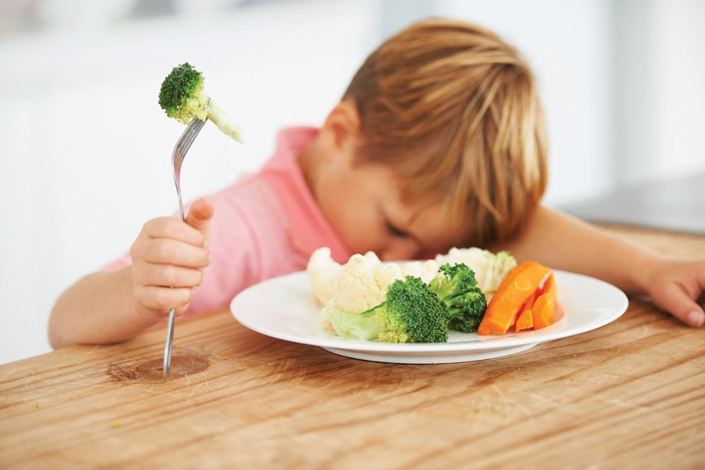 young boy eating vegetables reluctantly