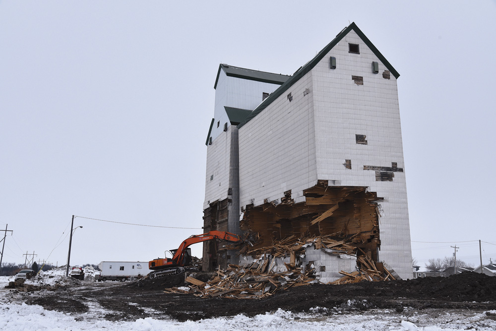 An elevator and crib annex at Sanford were built by Manitoba Pool in 1949 to replace ones destroyed by fire in September 1948. Closed in April 1996, it was sold into private hands. Demolition of the annex, seen here in January 2019, was akin to chopping down a tree. After making a large opening on one side, a push on the opposite side brought it down. It took 30 minutes from start to finish then the wood was hauled to the local landfill and burned. Four weeks later, the elevator fell in the same manner.