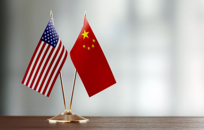 American and Chinese flag pair on desk over defocused background. Horizontal composition with copy space and selective focus.