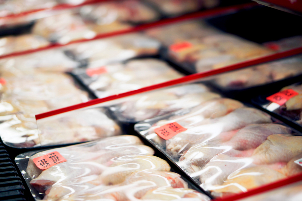 Packaged chicken legs in store refrigerator.