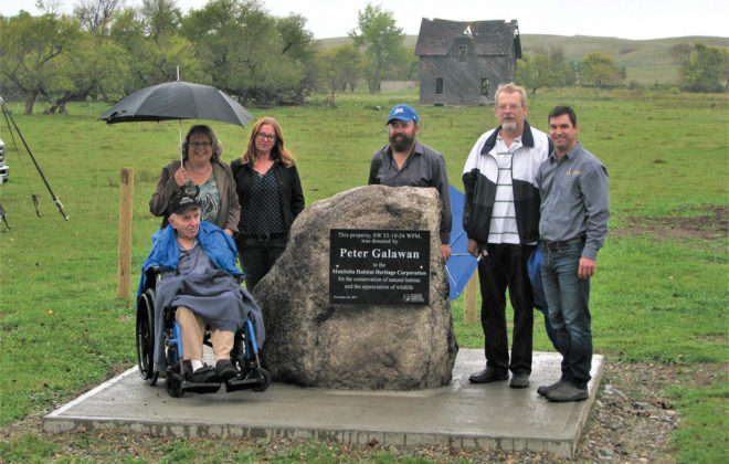 Peter Galawan (far left), poses with family members and MHHC staff pose with a cairn honouring Galawan for his donation. Left to right: Peter Galawan, Debbie McDowell (niece of Peter), Carol Graham (MHHC habitat conservation specialist), Ernest DeLaRonde (nephew of Peter), Gary Galawan (nephew of Peter) and Curtis Hullick (MHHC field manager).