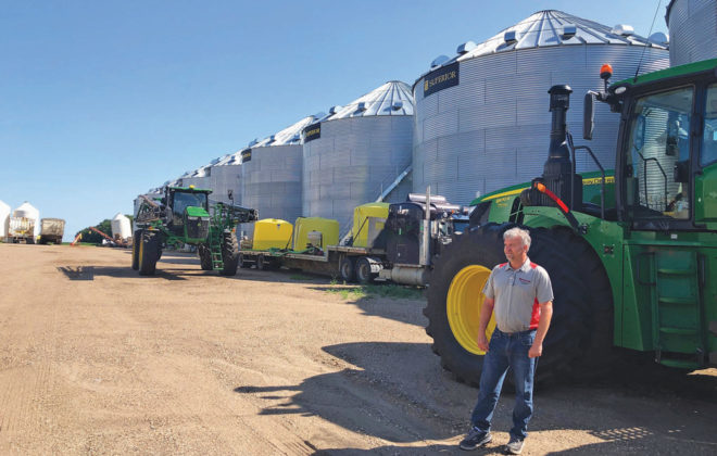 Farmer Mike Appert stands in front of some of his storage bins and machinery on his 48,000-acre farm in Hazelton, North Dakota on July22.