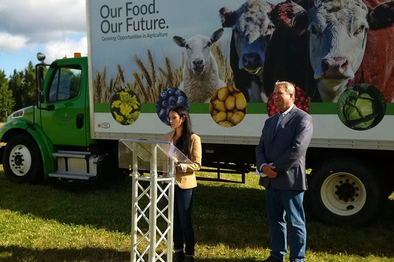 "Newfoundland and Labrador's minister of fisheries and land resources, Gerry Byrne, is shown here at right with Western Agriculture Centre research manager Sabrina Ellsworth and the department's ""Agri-Truck"" promotional vehicle at Pynn's Brook in September 2018. (Gov.nl.ca)"
