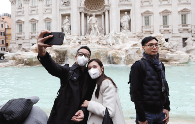 Tourists take a selfie in front of Rome's Trevi Fountain on Jan. 31 after two cases of novel coronavirus 2019-nCoV were confirmed in Italy.