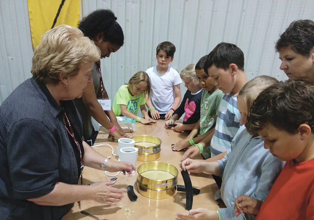 Attendees try their hand at wheat grinding during and earlier Amazing Agriculture 